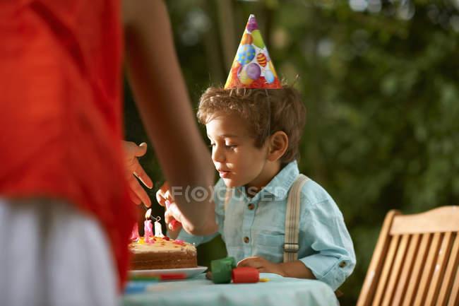 Мама з сином віє свічки на торті до дня народження на городі. — стокове фото