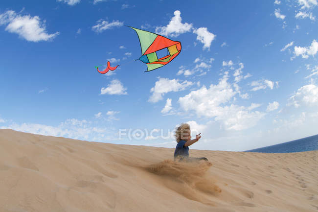 Boy flying kite on sand dune — Stock Photo
