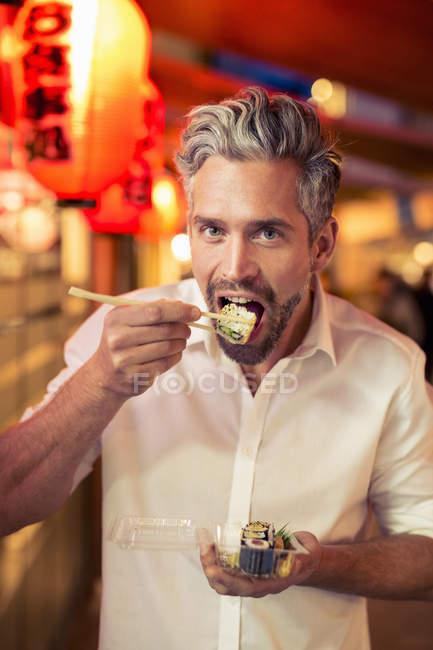 Uomo guardando la fotocamera con le bacchette per mangiare sushi — Foto stock