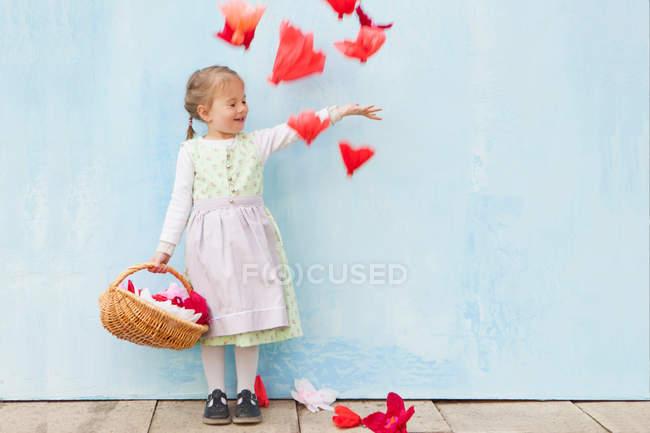 Menina sorridente brincando com flores de papel — Fotografia de Stock