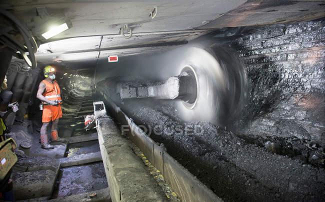 Les mineurs coupant du charbon au charbon semblent dans une mine profonde — Photo de stock