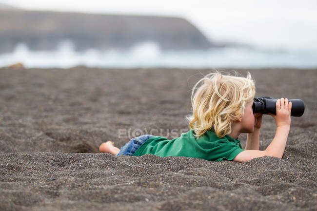 Boy using binoculars on beach — Stock Photo