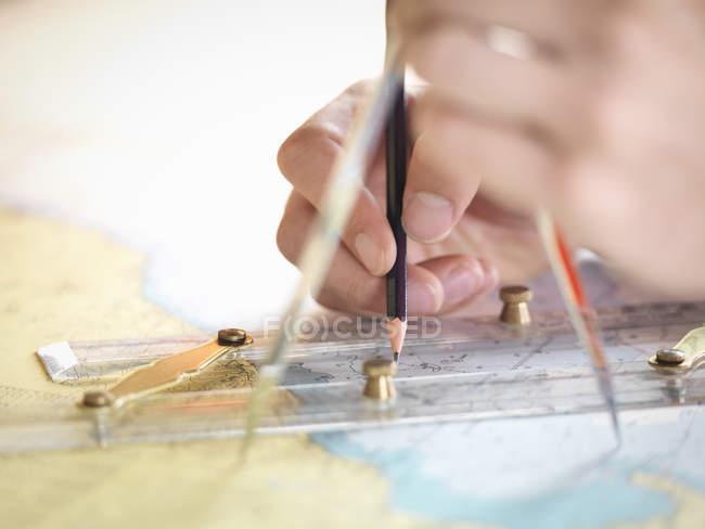 Close up of navigator checking charts on ship's bridge — Stock Photo