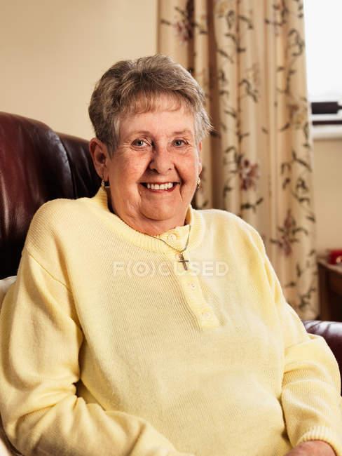 Улыбаясь Пожилая женщина, сидя в кресле — стоковое фото