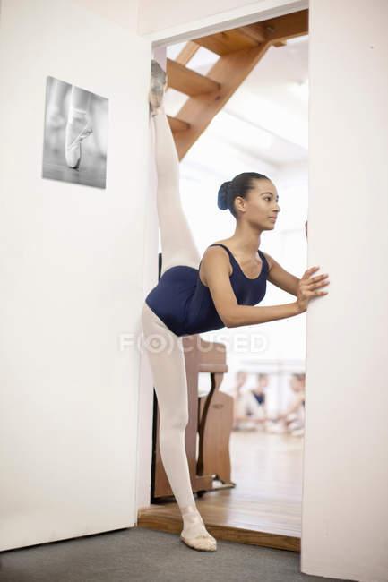 Teenage ballerina stretching in doorway — Stock Photo