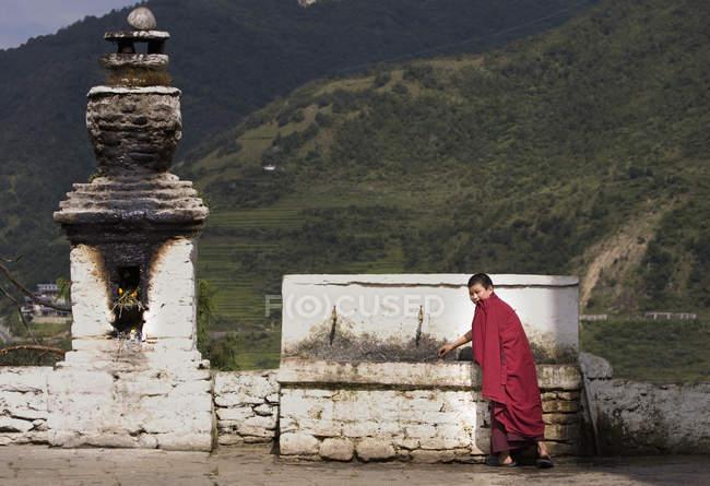 Porträt eines jungen buddhistischen Mönchs, der am Tempelbrunnen trinkt, Punakha, Bhutan — Stockfoto