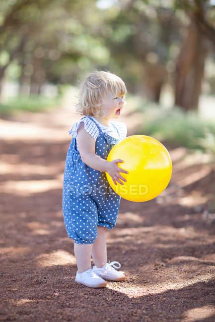 Niña con bola en camino de tierra - foto de stock