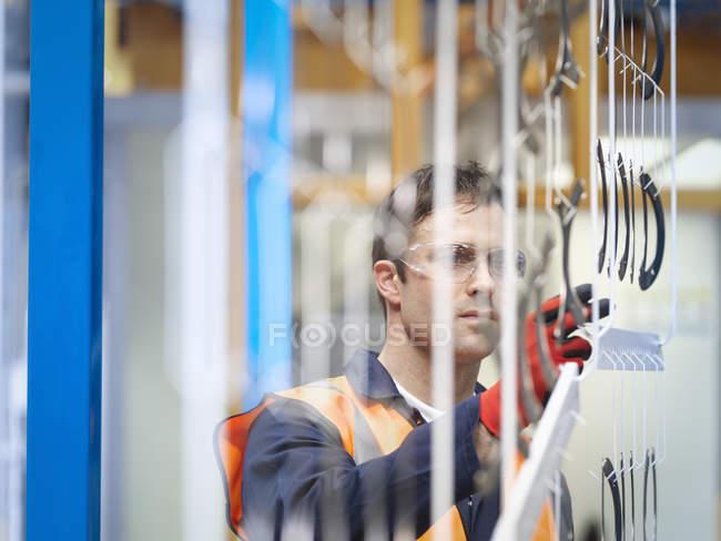 Рабочий осмотр окрашенных деталей на заводе листового металла — стоковое фото