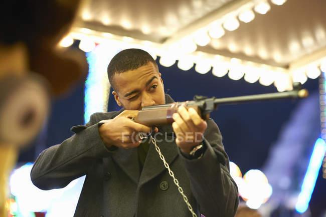 Homem adulto médio apontando o rifle na Galeria de tiro no parque de diversões — Fotografia de Stock