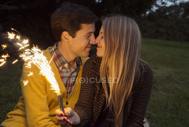 Young couple nose to nose in park holding sparkling firework — Stock Photo