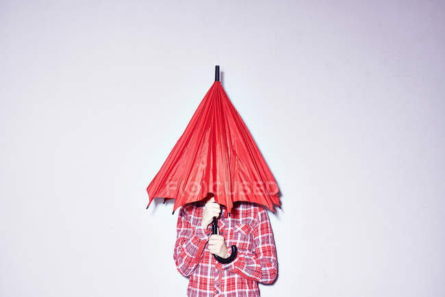 Woman holding red umbrella over her head — Stock Photo