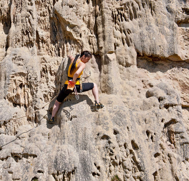 Female rock climber on rock face — Stock Photo