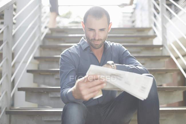 Empresário lendo jornal na escada — Fotografia de Stock