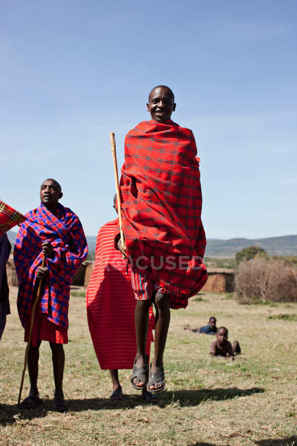 Maasai people walking in grassy field — Stock Photo