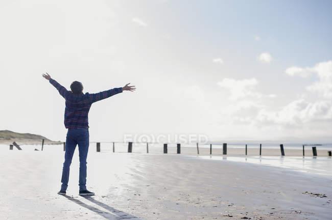 Молодой человек, стоящий на пляже с протянутыми руками, Брин-Сэндс, Сомерсет, Англия — стоковое фото