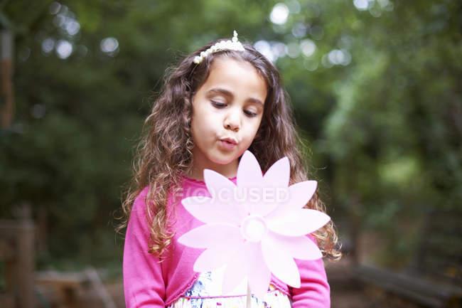 Chica soplando molinete de flores en fiesta de cumpleaños de jardín - foto de stock
