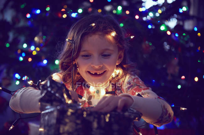 Girl surrounded by lights wrapping christmas presents at christmas — Stock Photo