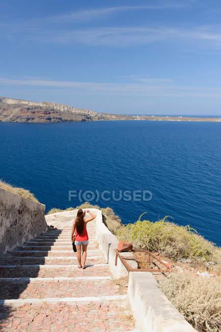 Turista femminile a piedi giù per scale, Oia, Santorini, Grecia — Foto stock