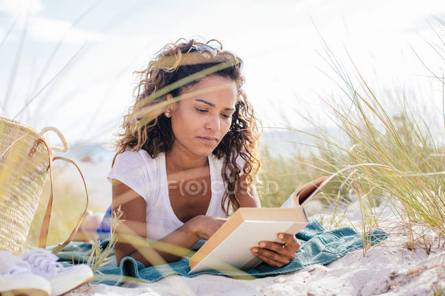 Young woman cross reading a book in beach dunes, Tuscany, Italy — Stock Photo