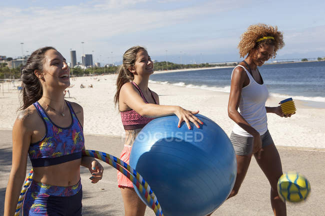 Three young women on beach with fitness ball — Stock Photo