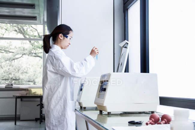 Femme scientifique en examinant l'éprouvette de laboratoire — Photo de stock