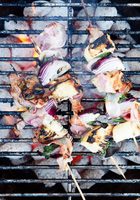 Skewers cooking on grill with vegetables — Stock Photo