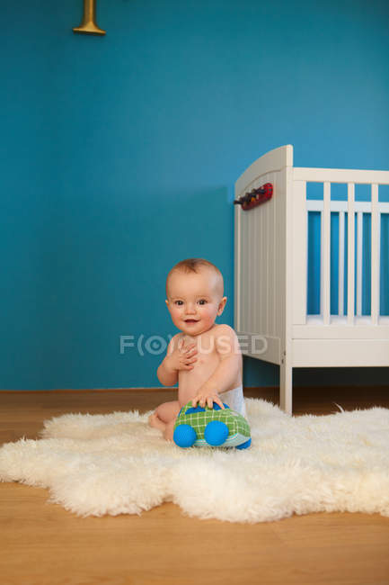 Toddler playing on rug in nursery — Stock Photo