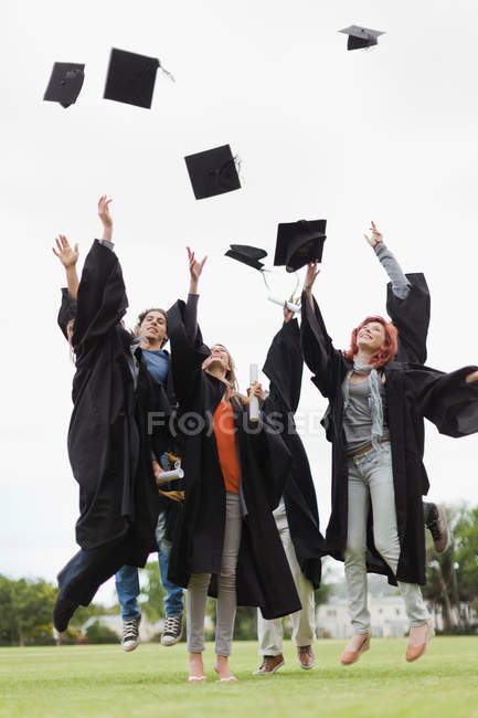 Выпускники бросают шапки в воздух — стоковое фото
