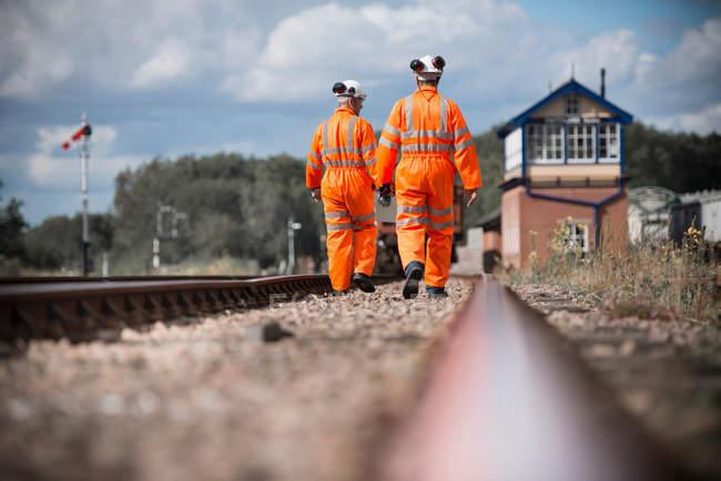 Travailleurs ferroviaires descendant et vérifiant les voies ferrées, vue arrière — Photo de stock