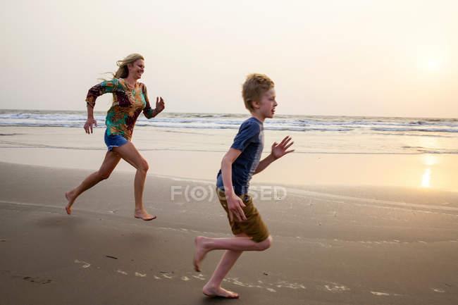 Мать и сын бегают по пляжу — стоковое фото