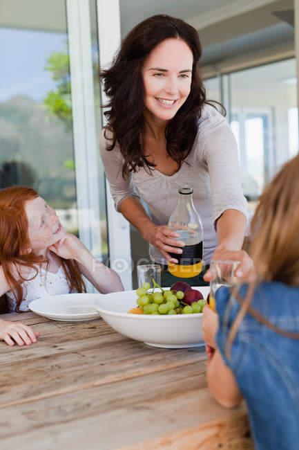 Мать кормит дочерей завтраком — стоковое фото