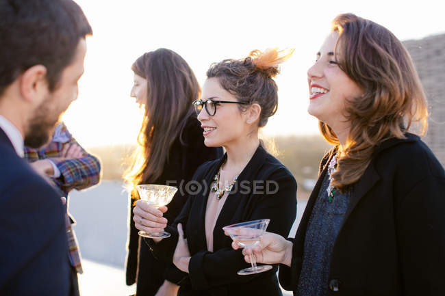 Группа друзей смеется и пьет на вечеринке на крыше — стоковое фото