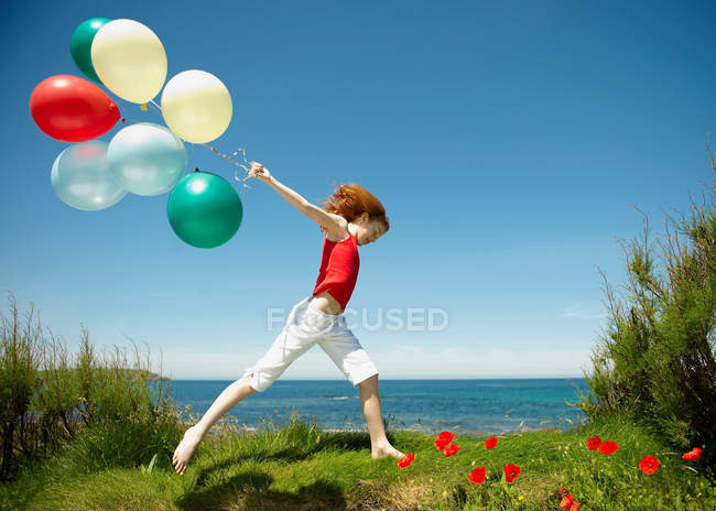 Young girl running with balloons — Stock Photo