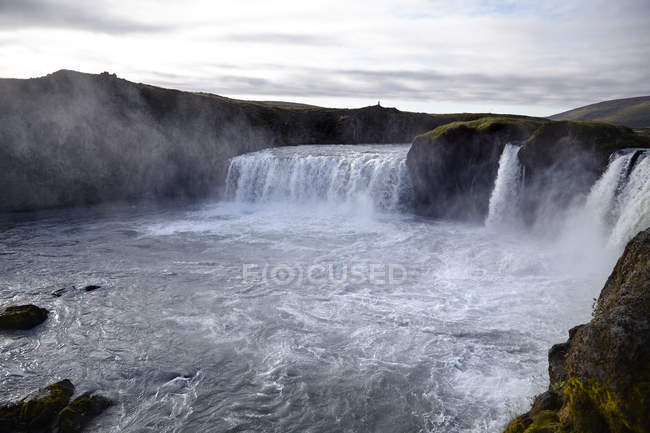 Landscape view of waterfalls under cloudy sky — Stock Photo