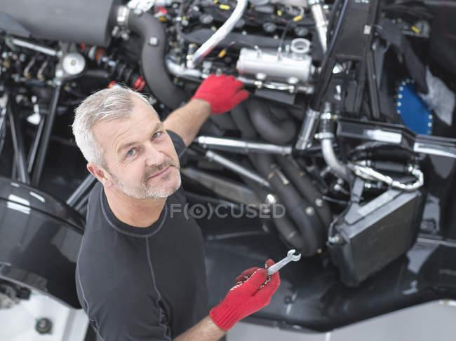Portrait d'ingénieur assemblant supercar dans une usine de voitures de sport, vue grand angle — Photo de stock