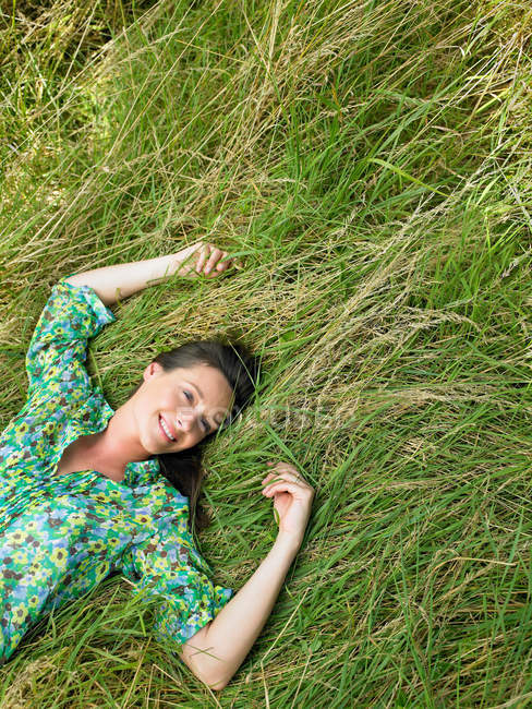 Woman laying down in a field — Stock Photo
