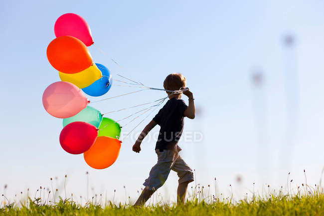 Boy with colorful balloons in grass — Stock Photo