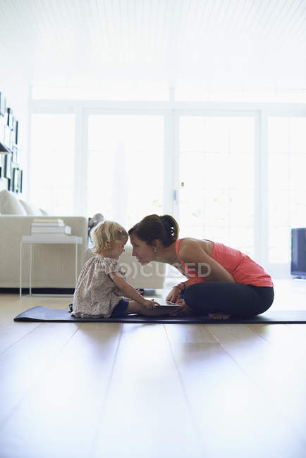 Mid adult mother and toddler daughter practicing lotus position in living room — Stock Photo