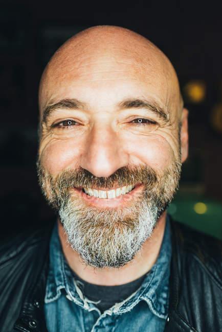 Портрет зрелого человека, в помещении, улыбающийся, крупный план — стоковое фото