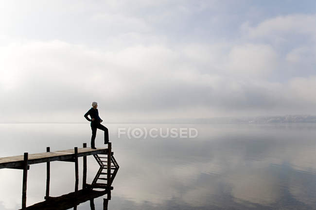 Pregnant woman standing on pier — Stock Photo