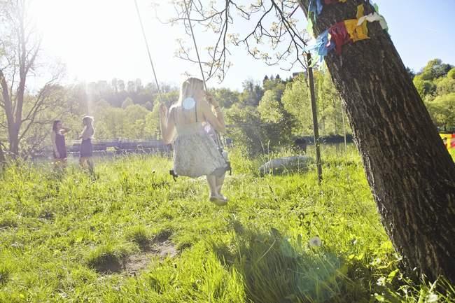 Молода жінка грає на гойдалки з друзями стоячи в зеленому сонячному полі — стокове фото
