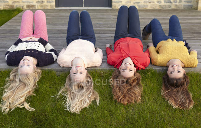 Four teenage girls lying on patio and looking back — Stock Photo