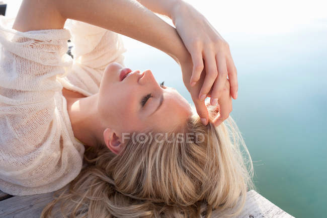 Close up of young woman lying on lake pier — Stock Photo