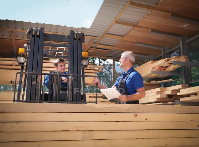 Travailleurs avec presse-papiers et chariot élévateur à fourche dans le magasin de menuiserie en bois — Photo de stock