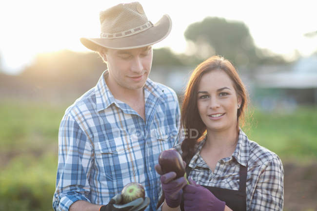 Young farm workers with aubergines grown on farm — Stock Photo