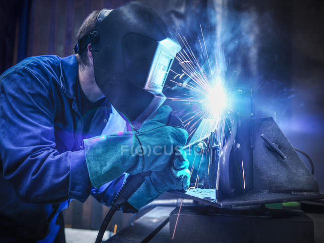 Welder wearing face mask and protective gloves in factory — Stock Photo