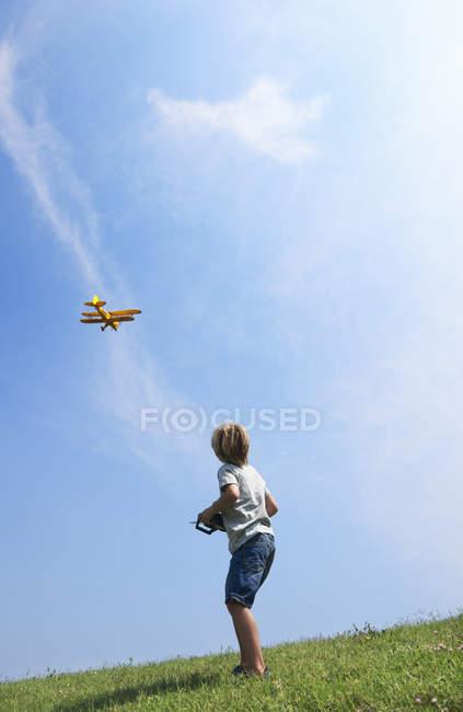 Vista trasera del niño pequeño avión modelo del vuelo - foto de stock