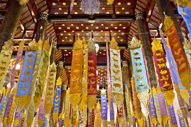 Buddhist temple interior with gold painted flags — Stock Photo