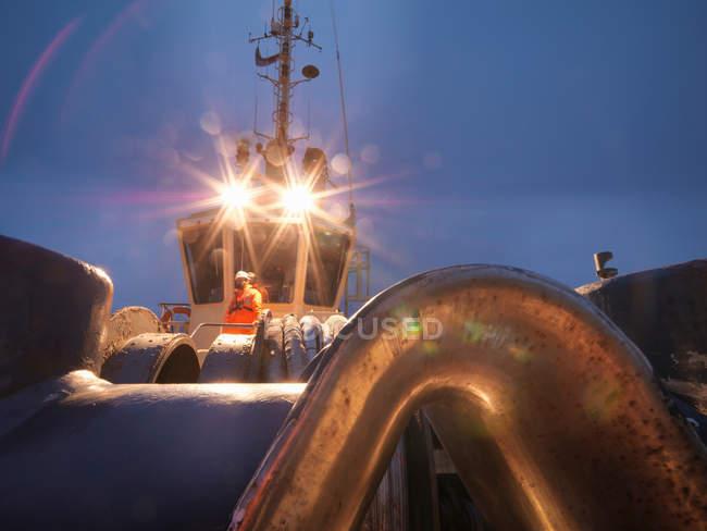 Буксир работника на буксир палубе в ночное время, объектив вспышки — стоковое фото
