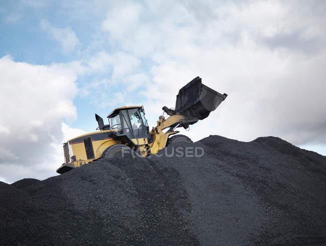 Creuseuse sur pile de charbon — Photo de stock